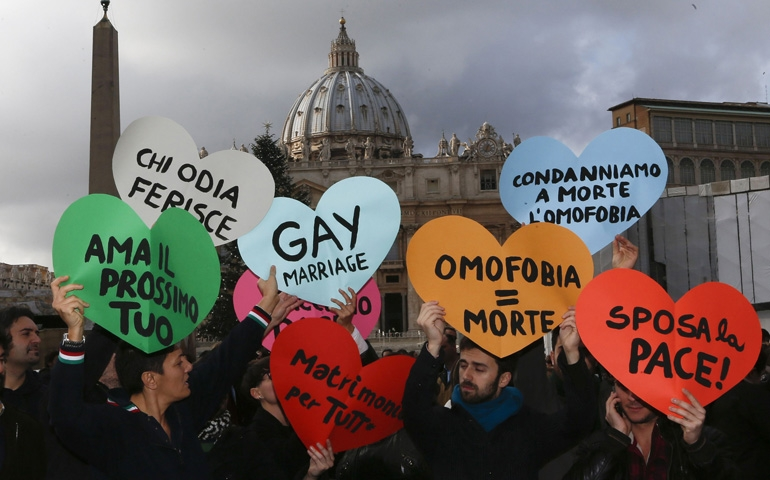 Members of a gay activist group hold up signs Dec. 16 outside St. Peter's Square at the Vatican. They demonstrated against part of Pope Benedict XVI's World Peace Day message, in which he affirmed Catholic teaching on marriage as the lifelong bond of a man and a woman. (CNS/Reuters/Alessandro Bianchi)