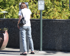 A campus visitor uses one of the parking meters.