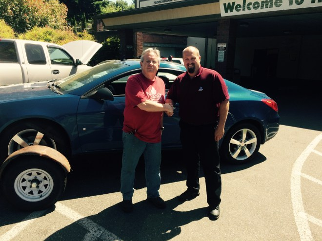 Peter Smith (left), Cascade High School automotive instructor poses with Scott Main, Shoreline's GM ASEP instructor in front of one of two vehicles donated to the high school through the GM ASEP program.