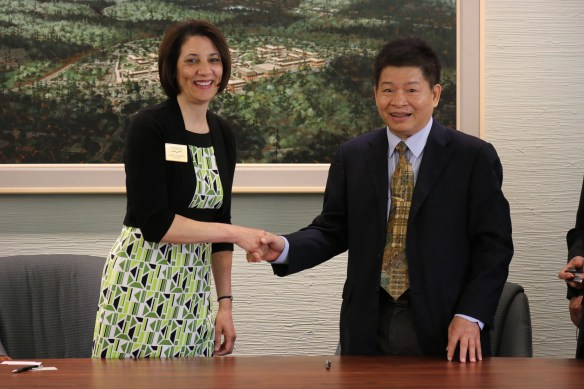 President Cheryl Roberts shakes hands with Vice President of Hainan Open University, Mr. Yuehua Xie, after signing a Memorandum of Understanding between the two schools.