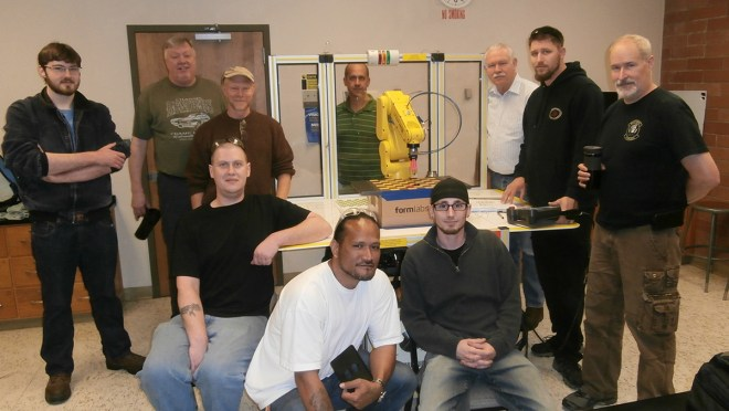 Students, staff, and faculty of Shoreline's CNC Machining program pose with a robotic arm.