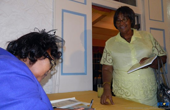 Margot Thomas signs a book for one of the women highlighted, the first female superintendent of prisons, Marjorie Grell.