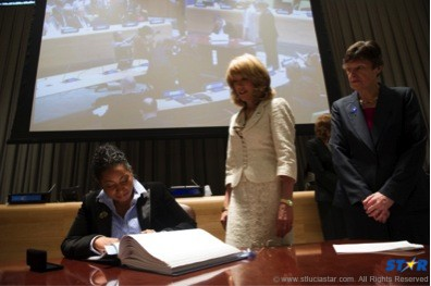 H.E. Menissa Rambally signs the treaty as Patricia O'Brien,United Nations Legal Counsel and Angela Kane, UN High Representative for Disarmament Affairs look on.