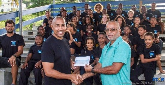 Eddie Hazel (r) of West Indies Shipping presents check to Lance Arnold representing the national swim team.