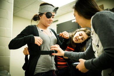 Vo, right, and Coffman, middle, place sensors on Psychology student Taylor Crowser. (Photo by Mark Brown)