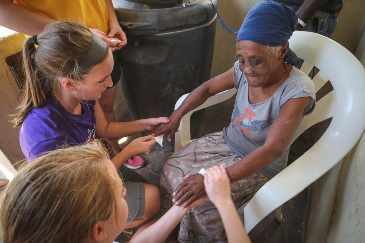 Lauren Ademite, top, and Nicole Pott, bottom, care for an elder orphan during a visit to Titanyen, the poorest rural village in Haiti. They brought her food, put lotion on her dry hands and shared prayers.