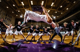 Marcus Alipate does his traditional pre-game flip before a men's basketball game.