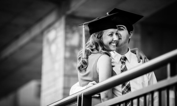 Students kiss as they pose for a photo beneath the Fowler Veranda in O'Shaughnessy Stadium prior to undergraduate commencement.