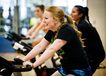Students in a wellness living learning community participate in a spin class,