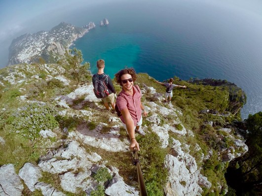 "Third place, Most Epic Selfie: Jacob Charbonneau, Capri, Italy. ""Mountain View: The photo was taken near the top of the mountain on the island of Capri. After hiking the terrain for a while, I stopped to take this selfie as we were making our descent to the edge of the cliffs. There is a haze in the pictures from the parting clouds due to how high up we were. The colors of the waters and the other part of the island were beautiful to look upon."""