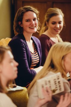 Law student Ashley Menzel smiles during the book discussion as fellow student Megan Parks looks on.