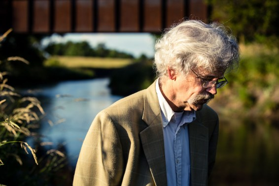 Art Cullen '80 stands next to the Raccoon River outside of Storm Lake, Iowa. Cullen was awarded a 2017 Pulitzer Prize for Editorial Writing for a series of editorials about a corporate agriculture lawsuit in Buena Vista County.