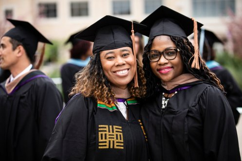 Jules Porter and a fellow student pose for a picture during the 2018 Graduate Commencement ceremony in O'Shaughnessy Stadium on May 18, 2018 in St. Paul.
