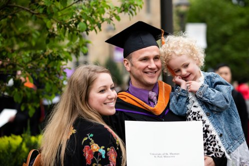 A graduate celebrates with family after the 2018 Graduate Commencement ceremony on the St. Paul campus on May 18, 2018 in St. Paul.