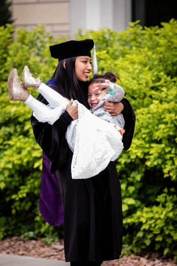A graduate lifts a smiling child after the 2018 Graduate Commencement ceremony on the St. Paul campus on May 18, 2018 in St. Paul.