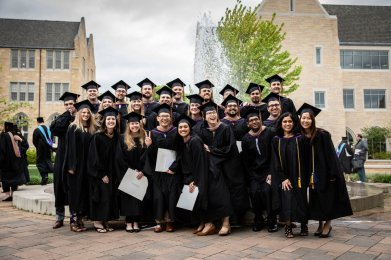 Student pose for a group photo on Monahan Plaza after the 2018 Graduate Commencement ceremony on May 18, 2018 in St. Paul.