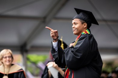 A graduating senior points at friends in the crowd as he crosses the stage to receive his diploma during the 2018 Undergraduate Commencement ceremony in O'Shaughnessy Stadium on May 18, 2018 in St. Paul.