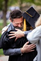 A graduating senior receives a hug from a family member during the 2018 Undergraduate Commencement ceremony in O'Shaughnessy Stadium on May 18, 2018 in St. Paul.