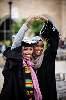 A graduating senior poses for a photo with a friend after the 2018 Undergraduate Commencement ceremony in O'Shaughnessy Stadium on May 18, 2018 in St. Paul.