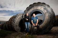 Amy Keele of TUB People, left, poses for a portrait with Jason Utgaard, right, next to large tires at a recycling facility in Salt Lake City, Utah, on April 19, 2018. Jason Utgaard, '07 Entrepreneurship, founded The Spotted Door, an online retailer that sells recycled and reclaimed products. Keele's company makes wallets and other products from recycled inner tubes. Utgaard sells the products on his site.