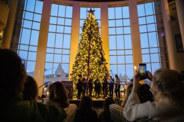 Attendees enjoy Christmas music and hold candle lights during the annual Tree Lighting Ceremony in the Anderson Student Center on December 4, 2018.
