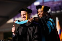 A student gives a thumbs up while being hooded by School of Education Dean Dr. Kathlene Holmes Campbell during the 2019 Graduate Commencement Ceremony in O'Shaughnessy Stadium on May 25, 2019 in St. Paul.