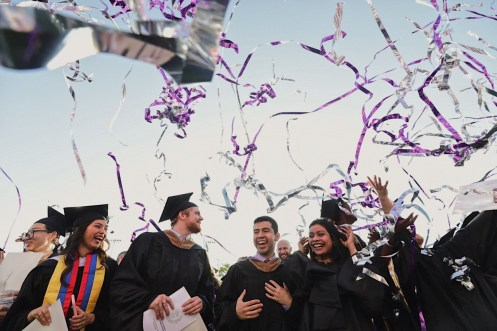 Confetti flies above graduates during commencement on May 25.