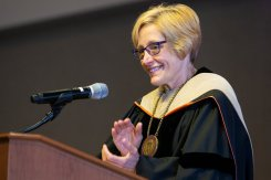 President Julie Sullivan applauds during the Dougherty Family College commencement.