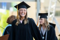 A joyous student smiles after receiving their diploma.
