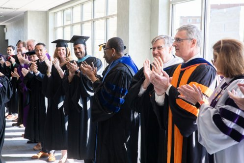 Administrators and faculty applaud during the Dougherty Family College commencement.