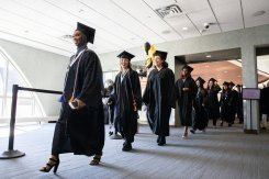 Dougherty Family College students walk through the Anderson Student Center into commencement.
