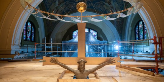 A large crucifix in the Chapel of St. Thomas Aquinas peaks through a layer of scaffolding.