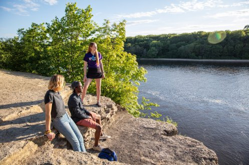 Students Sarah Benoy, Shukrani Nangwala and Mackenzie Stahl talk on the river bluffs overlooking the Mississippi River.