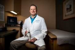 Orthopedic surgeon and University of St. Thomas alumni, Nicholas Weiss '92, sits for a portrait holding a knee replacement model in the Twin Cities Orthopedics office in Stillwater.