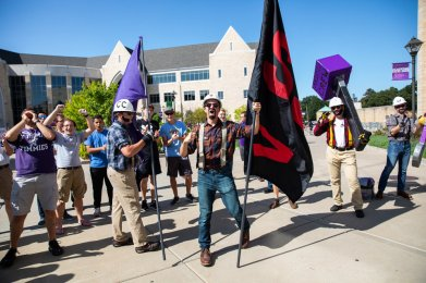 "Members of ""Caruso's Crew"" celebrate during the annual March through the Arches to celebrate the start of the school year and the arrival of a new class of freshmen on campus on September 3, 2019, in St. Paul."