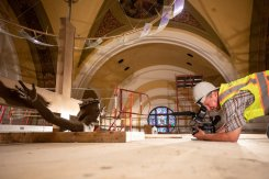 Videographer Brad Jacobsen films a crucifix sticking through scaffolding in the Chapel of St. Thomas Aquinas during renovations on July 18, 2019, in St. Paul.