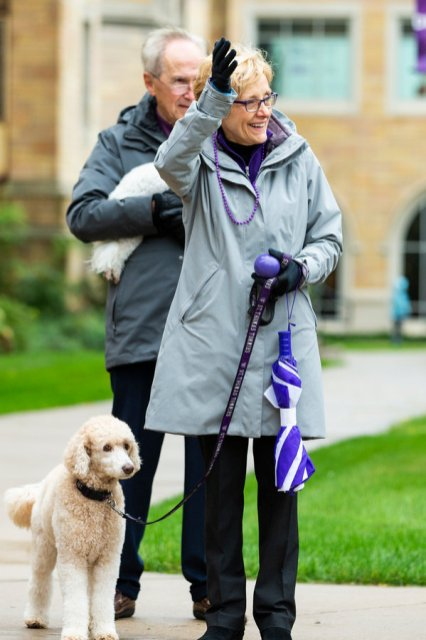 University president Julie Sullivan waves, accompanied by her dog, Bella, while students march in the homecoming parade through campus during the Tommies Homecoming and Family Weekend Celebration. Liam James Doyle/University of St. Thomas