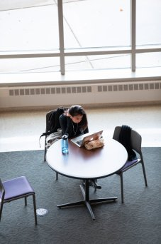 A student studies at a table in the Anderson Student Center atrium. Mark Brown/University of St. Thomas