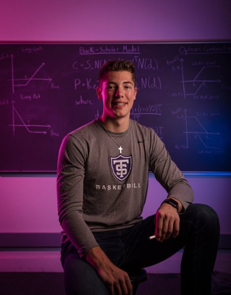 Senior Tommy Anderson, an Actuarial Science major and basketball player, poses for a photo in front of actuarial equations on a blackboard. Mark Brown/University of St. Thomas