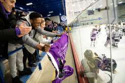 Fans cheer on the Tommies during a women's hockey game. Mark Brown/University of St. Thomas