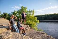 Students Sarah Benoy, Shukrani Nangwala and Mackenzie Stahl on the river bluffs overlooking the Mississippi River. Mark Brown/University of St. Thomas
