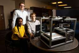 "Engineering students Meheret Tadesse, Henry Martinson and Charles Lundquist pose with the ""Tactile Diagram Scanner"" technology they developed. Liam James Doyle/University of St. Thomas"