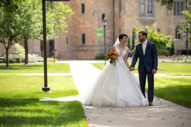 A couple getting married on campus walks across the quad. Mark Brown/University of St. Thomas