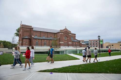 Students walk through the upper quad and past the Iversen Center for Faith and Aquinas Chapel.