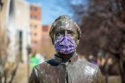 The statue of Archbishop John Ireland stands on the quad wearing a mask during the coronavirus pandemic.