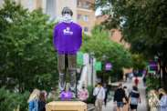 The statue of Archbishop John Ireland stands adorned with a purple shirt, mask and care packet that was available to all students on the St. Paul campus. Liam James Doyle/University of St. Thomas