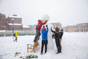 Students make a large snowman on the upper quad during a fall snowstorm in October. Mark Brown/University of St. Thomas
