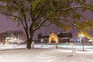 Aquinas Chapel and the Iversen Center for Faith glow at night during the first measurable snowfall of the year on October. Mark Brown/University of St. Thomas