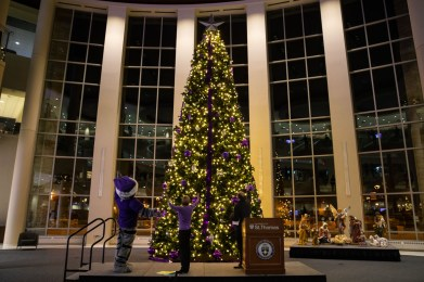 A holiday tree with decorations and lights stands in the Anderson Student Center.