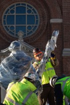Workers unwrap the new sculpture of St. Thomas Aquinas by Canadian artist Timothy P. Schmalz. Mark Brown/University of St. Thomas